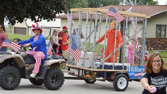 A Hillary Clinton impersonator, Adam Corky, being pulled in a makeshift prison cell by an ATV driven by Kyle Julin in Arcadia on Saturday.