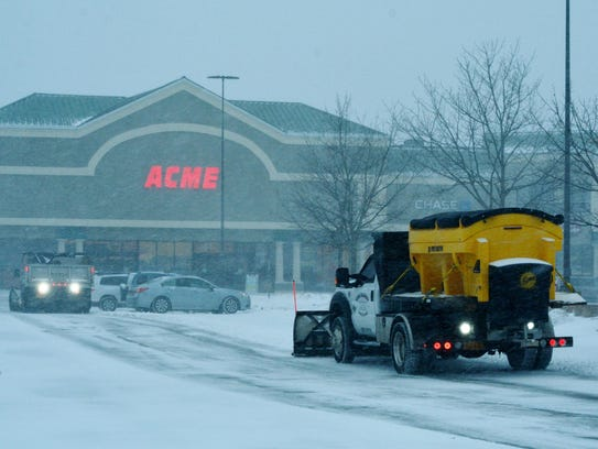 Workers clear the first two inches of snow Thursday
