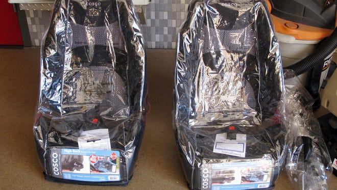 Two brand new child car safety seats sit wrapped in plastic prior to installation.