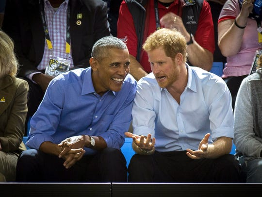 Former President Barack Obama and Prince Harry watch