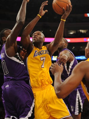 Los Angeles, CA, USA; Los Angeles Lakers forward Lamar Odom (7) goes up for a layup defended by Sacramento Kings center Samuel Dalembert (10) at the Staples Center.