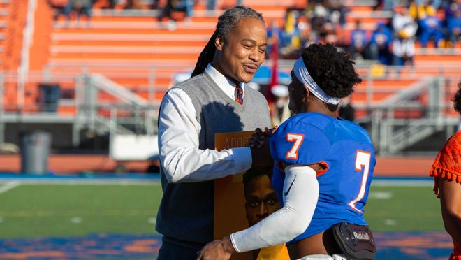 Savannah State Athletics Director of Athletics Opio Mashariki greets senior football player Adorian Beach on senior day during the 2019 season.
