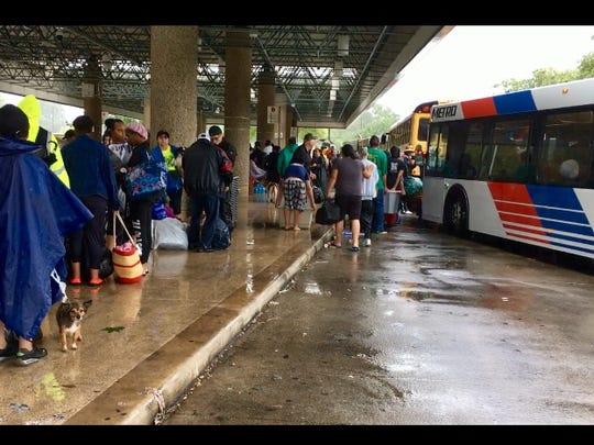 Evacuees at the Hardy-Ley Bus Station wait for Houston Metro buses to take them to the George R. Brown Convention Center.
