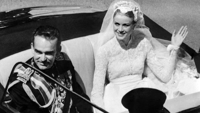 A photo taken on April 19, 1956, shows Prince Rainier III of Monaco and U.S. actress and princess of Monaco Grace Kelly saluting the crowd as they leave Saint Nicholas' Cathedral after their wedding ceremony in Monaco. Monaco's royals on May 2, 2014, accused those behind a biopic (starring Nicole Kidman as their mother Grace) of hijacking their family history, just days before the film premieres at the Cannes Film Festival. In a statement, Prince Albert II and Princesses Caroline and Stephanie said the film did not accurately portray events involving their mother, the Hollywood actress who married Monaco's Prince Rainier III in 1956.