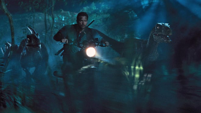 "This photo provided by Universal Pictures shows, Chris Pratt as Owen leading the raptors on a mission in a scene from the film, ""Jurassic World,"" directed by Colin Trevorrow, in the next installment of Steven Spielberg's groundbreaking ""Jurassic Park"" series. The Universal Pictures 3D movie releases in theaters on June 12, 2015. (ILM/Universal Pictures/Amblin Entertainment via AP)"