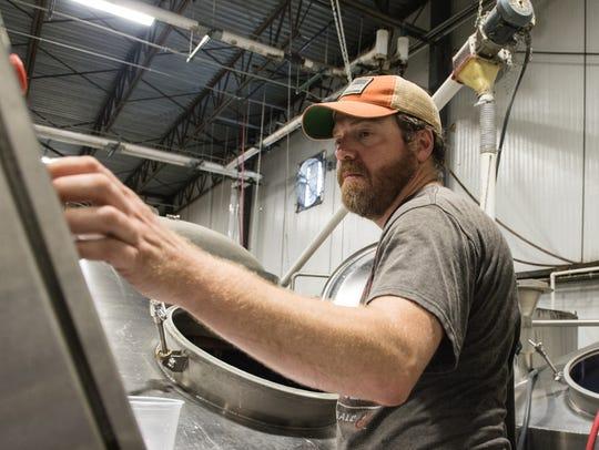 Brewmaster Jimmy Sharp operates a mash tun at Evolution