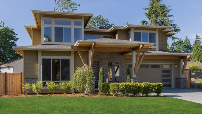 Large windows and a sleek hipped roof give exceptional curb appeal to this modern design.