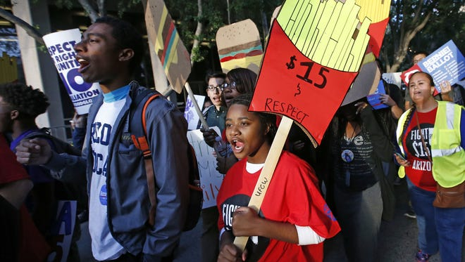 Several hundred people march in Phoenix in support of raising the minimum wage.