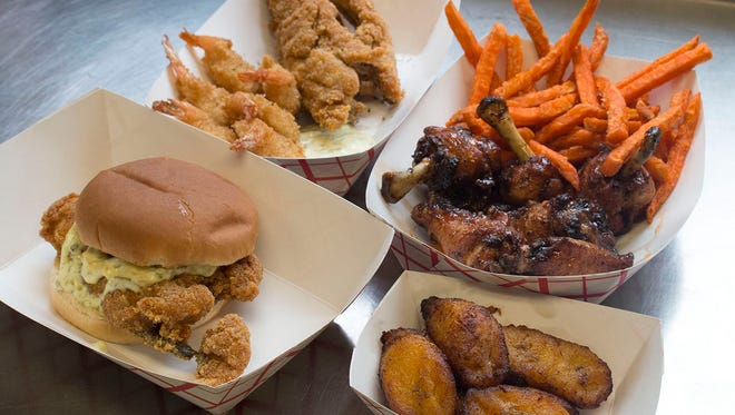 Rondell Donaldson and his fiancee Renee Campbell own the food truck/catering company,  Dishes from Caribbean Soul include (clockwise from bottom left) a fried whiting sandwich, whiting and shrimp, Bang Bang Wings with sweet potato fries, and fried plantains.