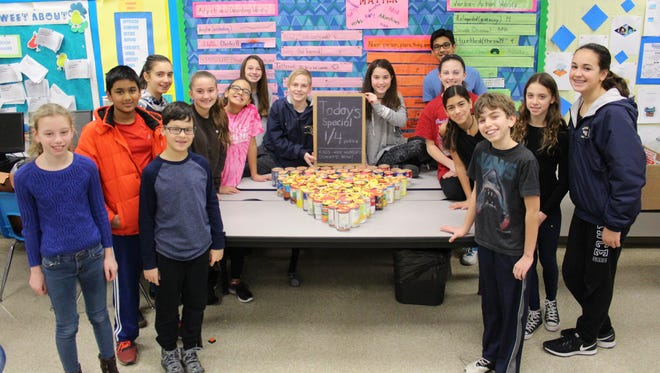 Sixth-graders in Emily Baker's class at Warren Middle School create a slice of pizza out of canned goods as part of a character education project.