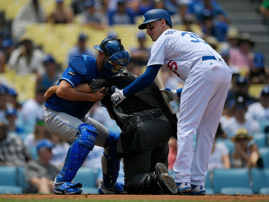 Home plate umpire Kerwin Danley, center, is helped to the ground by Kansas City Royals catcher Drew Butera, left, and Los Angeles Dodgers' Cody Bellinger after he was hit by a foul tip during the first inning of a baseball game, Sunday, July 9, 2017, in Los Angeles. Danley left the game later and was replaced. (AP Photo/Mark J. Terrill)