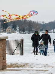"Dustin and Emily Connors of Pewaukee walk back to shore with their son Owen during Silly Willyz ""Fly a Kite on Ice"" event in 2016. The local toy store will welcome guests to enjoy its kites for free again Saturday, Feb. 3."