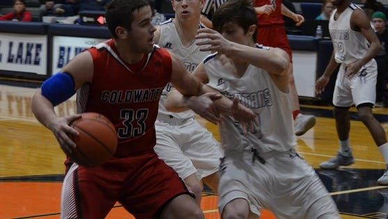 Coldwater's Cole Targgart drives to the basket against Lakeview defender Harrison Jewell in this Class A district semifinal.