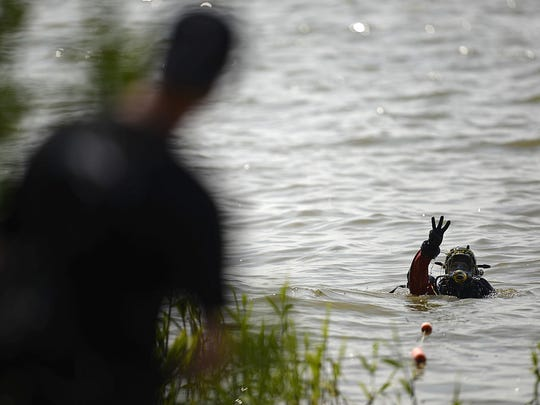 Members of the Green Bay Police Department dive team search the waters off Communiversity Park in Green Bay on Wednesday, June 10, 2015.