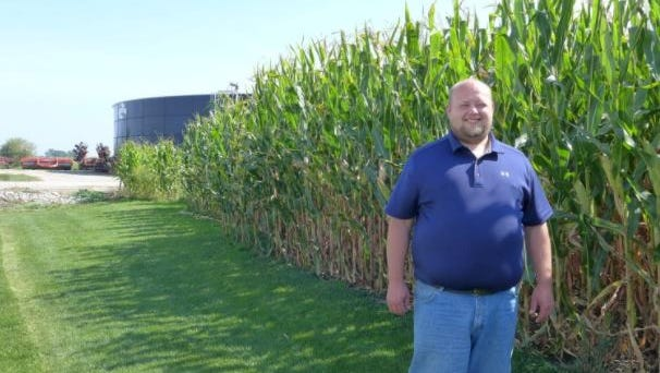 """Josh Hiemstra, a Fond du Lac farmer, has been using software developed at UW–Madison for more than a dozen years to track soil fertility and plan applications of fertilizer and liquid manure, stored in the """"big blue lagoon"""" in the background."""