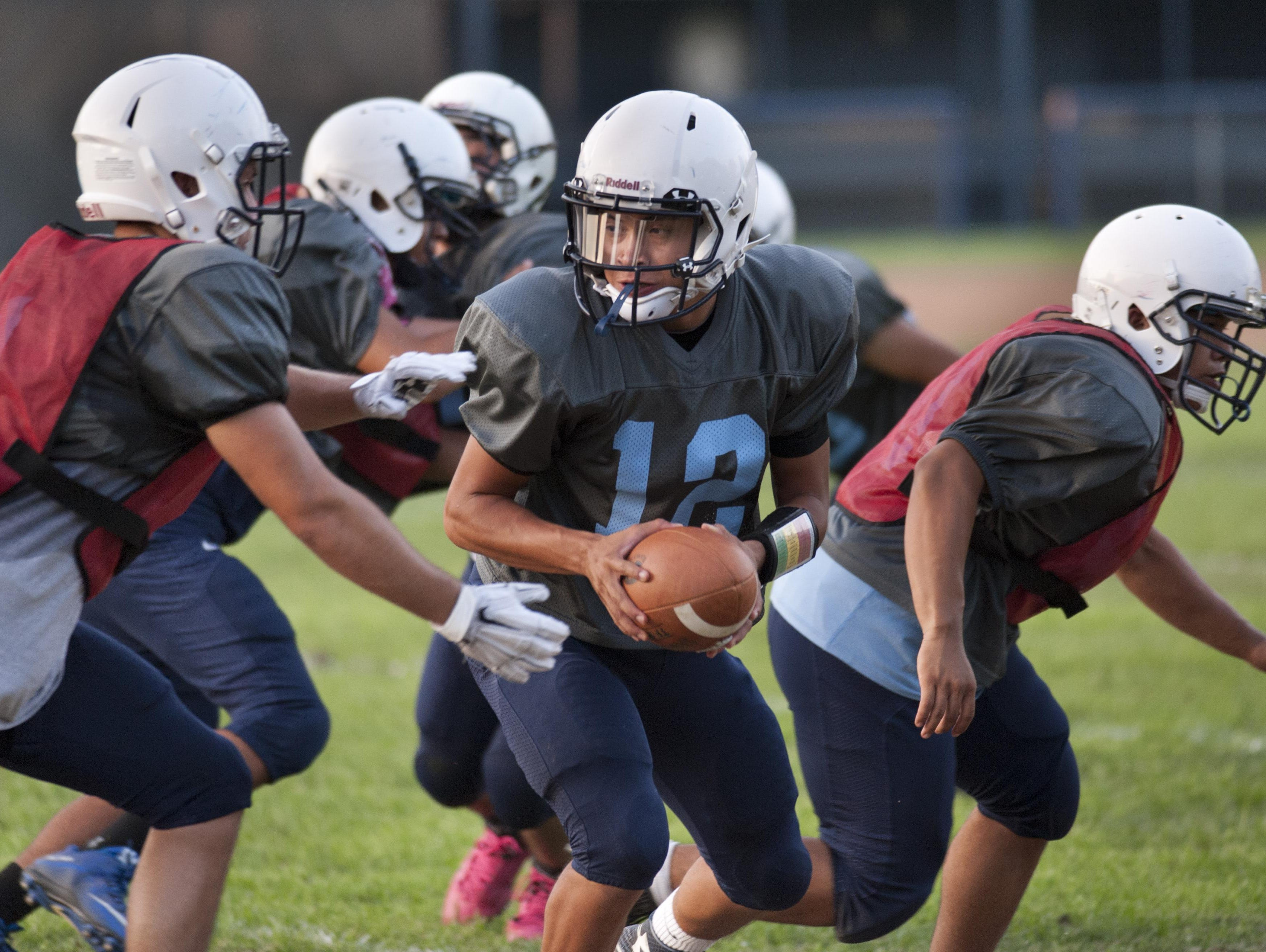 Redwood junior quarterback Frankie Ayon runs a play during practice on Tuesday.