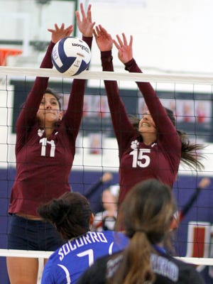 Lady Cat sophomores Vanessa Garcia (11) and Joleen Perez (15) team on the block against Socorro on Saturday. The Deming High varsity defeated the Warriors in three straight games, 25-12, 25-18 and 25-15 at DHS Wildcat Gym.