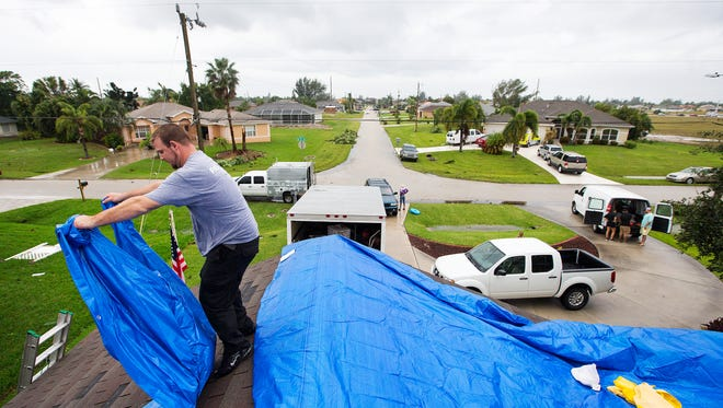 Ryan Tomten spreads tarp on the roof of Cheryl Cooper's home Sunday in Cape Coral. Hundreds of Cape homes were severely damaged by a tornado late Saturday evening.