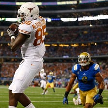 Texas Longhorns tight end M.J. McFarland (85) makes a touchdown catch against the UCLA Bruins during the second quarter at AT&T Stadium in Arlington on September 13, 2014.