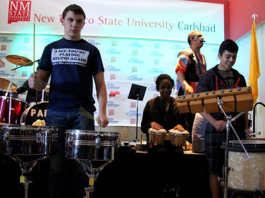 Early College High School students were invited to try their hands at various percussion instruments during a performance by Pablo Mendoza, at right in the background.