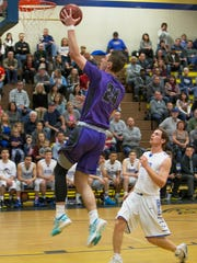 Spanish Springs Cougars Josh Prizina drives past Reed Raiders Lincoln Turner fora lay-up in their basketball game played on Friday at Reed.
