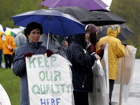 Teacher Sue Tester stands under an umbrella with other