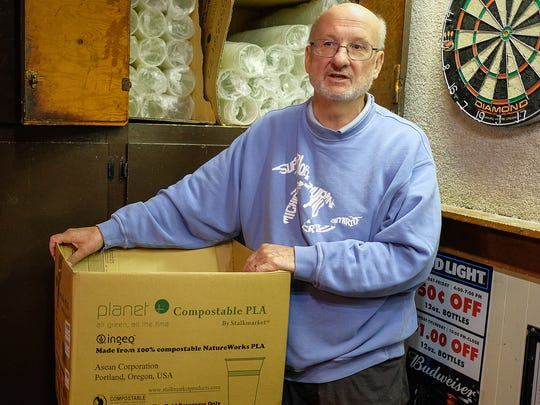 Joe Bell, co-owner of The Peanut Barrel in East Lansing, re-stocks a cabinet with compostable beverage cups and talks about his efforts to make his establishment more green Saturday, June 23, 2018. He is switching as many of consumables from plastic to more compostable products.