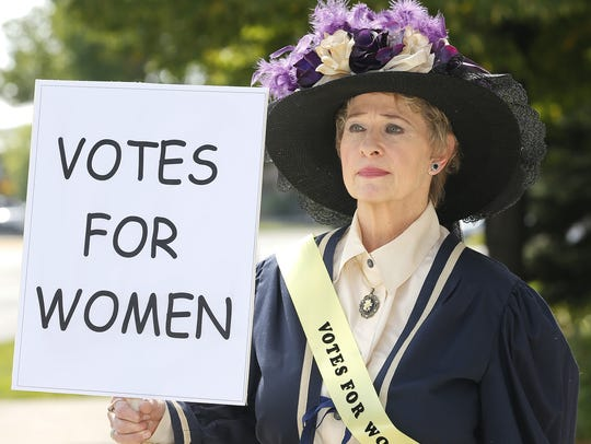 "Women suffragist re-enactor Lyn Galvas holds a ""Votes for women"" sign."
