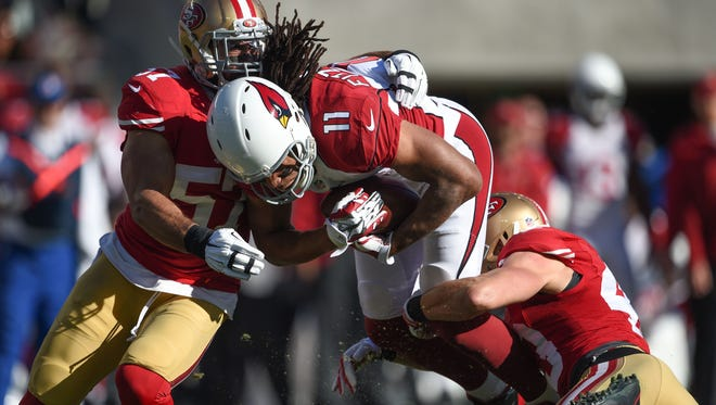 December 28, 2014; Santa Clara, Calif; Arizona Cardinals wide receiver Larry Fitzgerald (11) is tackled by San Francisco 49ers inside linebacker Michael Wilhoite (57) and strong safety Craig Dahl during the first quarter at Levi's Stadium.