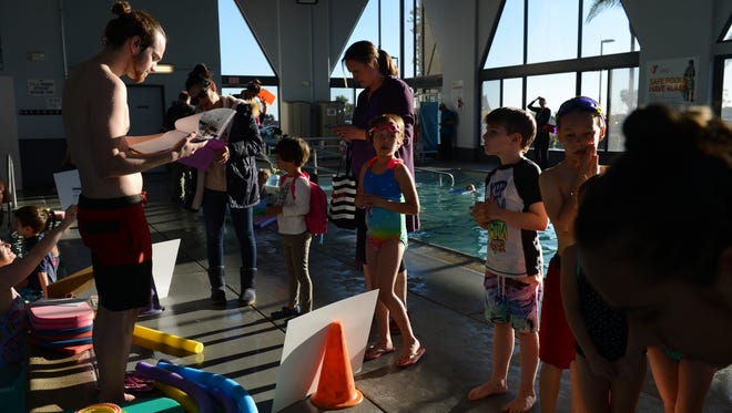 Shaun Rhodes, left, checks students in for his swimming class at the Ventura Family YMCA.