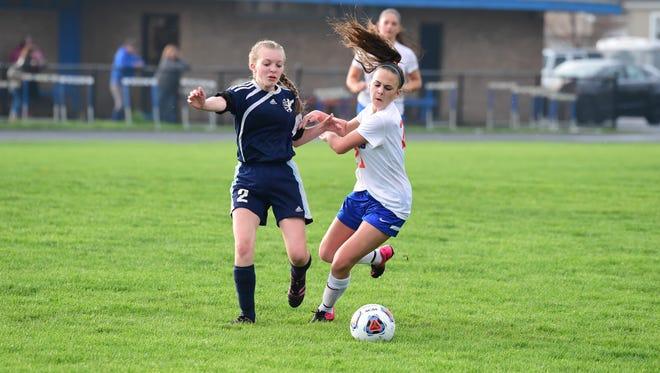 Garden City's Faith Staley (right) tries to maneuver away from Redford Thurston's Andrea Gartner during Wednesday night's girls soccer game.