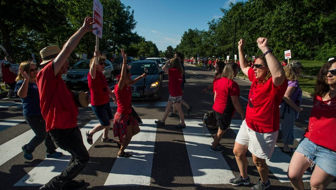 Nurses dance across the crosswalk during red light on East Avenue in Burlington near UVM Medical Center after hundreds walked out on strike Thursday morning, July 12, 2018. At odds over pay, staffing levels and other issues, the nurses union and the hospital administration have been unable to come to an contract agreement.