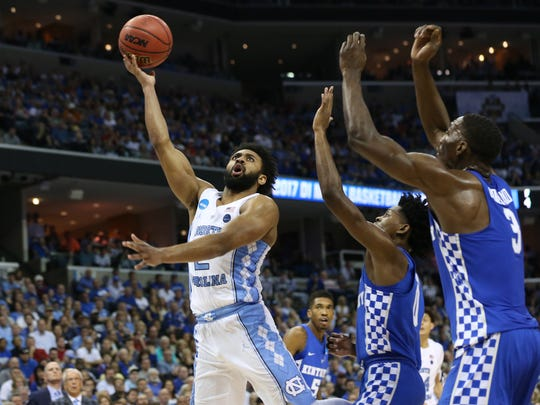 North Carolina Tar Heels guard Joel Berry II (2) shoots against Kentucky Wildcats guard De'Aaron Fox (middle) and forward Edrice Adebayo (3) in the second half during the finals of the South Regional of the 2017 NCAA Tournament at FedExForum.