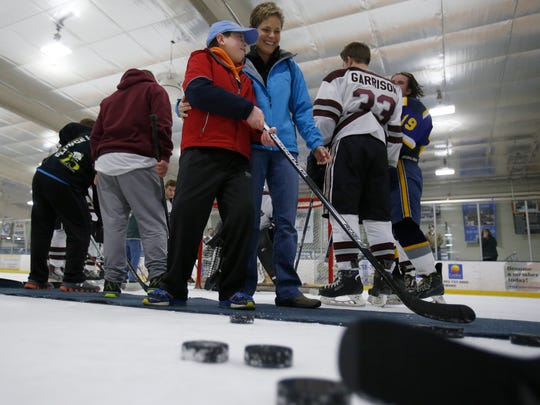 "Ruth Lavelle helps out with her son Matt as ""buddies"" and the high school teams in the DFRC's Hockey for a Cause doubleheader spend some ice time together at the University of Delaware's Gold Ice Arena Wednesday."
