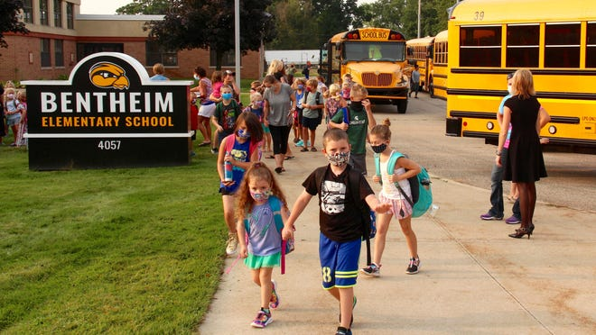 A group of students make their way from the bus into Bentheim Elementary School Wednesday, Aug. 26, for the first day of the 2020-21 school year.