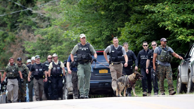 Law enforcement officers walk along a road as the search continues for two escaped prisoners from the Clinton Correctional Facility in Dannemora, on Monday, June 22, 2015, in Owls Head, N.Y. In the more than two weeks since inmates David Sweat and Richard Matt escaped, more than 800 law enforcement officers have gone door-to-door checking houses, wooded areas, campgrounds and summer homes.