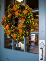 A fall-themed wreath adorns the door at Caroline &