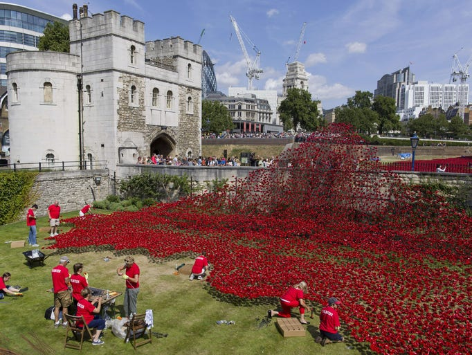 """Volunteers install porcelain poppies as part of the art installation """"Blood Swept Lands and Seas of Red"""" by ceramic artist Paul Cummins and theater stage designer Tom Piper marking the centenary of the start of World War I at the Tower of London on Aug. 3."""