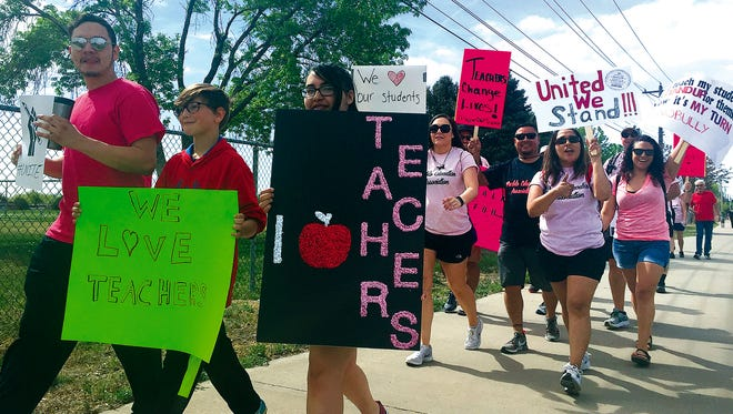 Teachers from Pueblo Academy of Arts in Pueblo, Colo., march along Pueblo Bouelevard starting a four-mile, two-hour trip to the Pueblo City Schools (D60) offices on Monday, May 7, 2018. Teachers in Pueblo went on strike Monday, shutting down schools in a dispute over how much they should be paid for the school year that's nearly over. (Anthony A. Mestas/The Pueblo Chieftain via AP)
