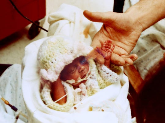 A picture of David Flory taken on Feb. 10, 1980, holding the hand of his very tiny daughter Kasey Tuffy (Flory) Hadd who was born as a preemie on Christmas Eve 1979 weighing in at 15 oz at Sparrow Hospital in Lansing, Michigan.  Flory family photo handout