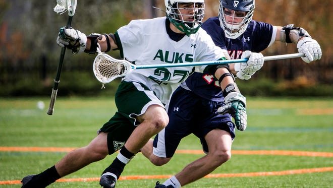 Archmere's Ben Revak (left) runs past a Wilmington Friends defender on April 7. Revak, the state's Player of the Year, scored six goals in the Auks' 13-8 win.