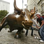 A passerby, right, helps Thuy Hoang of San Jose mount a statue of a bull at the foot of Broadway in the financial district on Aug. 16, 2004, in New York. The statuesque bull, which represents a bullish stock, is a good luck charm for stockbrokers, who have been known to swipe the bronze animal with their briefcases for good luck on the way to work.