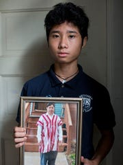Htee Moo, 13, holds a portrait of his father, Jay Ro, at the family's new home on the south side of Milwaukee on Sept. 6, 2017, in Milwaukee Wisconsin.