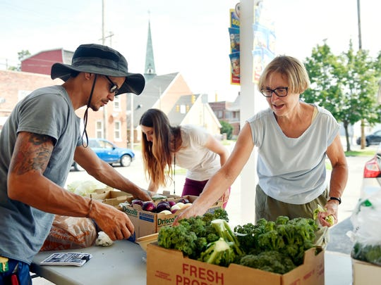 "From left, seasonal helper Erick Negron, York City Bureau of Health community health specialist Paige Nenstiel and York Fresh Food Farms treasurer Metta Barbour arrange produce for York Fresh Food Farms' Produce Markets in association with the Healthy Corner Store Initiative Wednesday, Aug. 2, 2017, at Pak's Food Market in York. York Fresh Food Farms, managed by Bruce Manns, is a nonprofit that operates one farm plot in the Parkway neighborhood and will soon cultivate a larger plot off Roosevelt Avenue. Much of the produce is distributed through three stores in the city to alleviate food desert issues, in a partnership with the York City Bureau of Health, while the rest is sold to local restaurants or donated to shelters, missions or other nonprofit organizations. ""Food is a common denominator in so many things. It's like a peace thing,"" Manns said. ""And that's what I like to do. There's a need for it."""