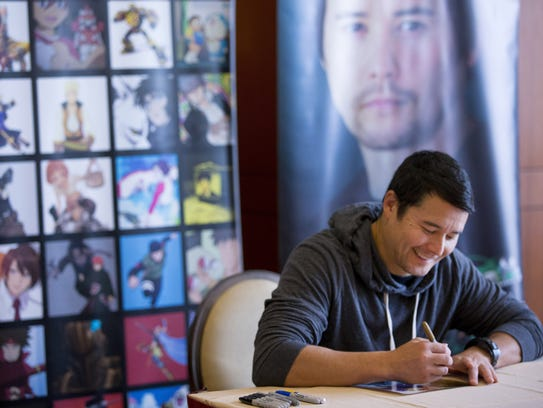 Actor Johnny Yong Bosch signs autographs during the