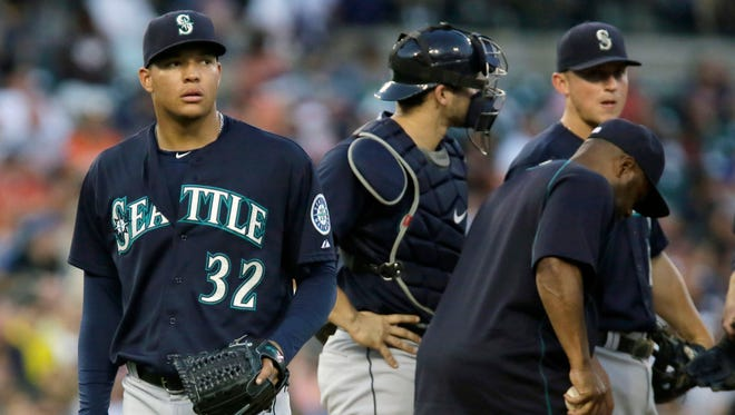 Seattle Mariners' Taijuan Walker (32) heads for the dugout after being pulled by manager Lloyd McClendon, right, after giving up a single to Detroit Tigers' J.D. Martinez during the fifth inning of a baseball game Tuesday, July 21, 2015 in Detroit.