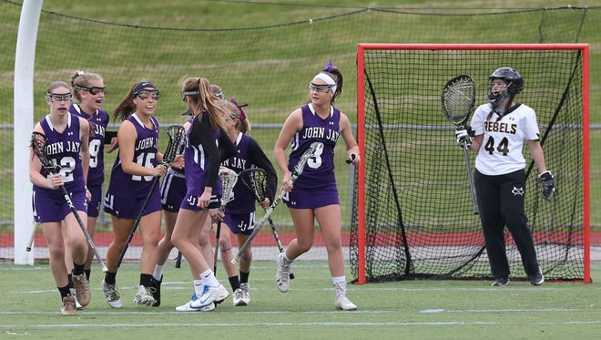 John Jay players celebrate a first half goal by Jacque Manno (15) against Lakeland/Panas during a lacrosse game at Walter Panas High School in Cortlandt April 29, 2016. John Jay won the game 14-11.