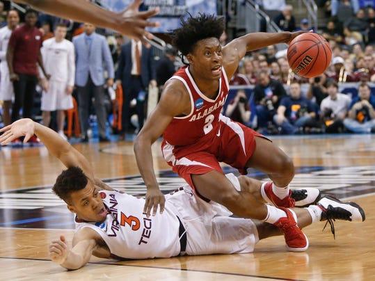 Alabama's Collin Sexton (2) tumbles over Virginia Tech's Wabissa Bede (3) during the second half of an NCAA men's college basketball tournament first-round game Thursday, March 15, 2018, in Pittsburgh. Alabama won 86-83. (AP Photo/Keith Srakocic)