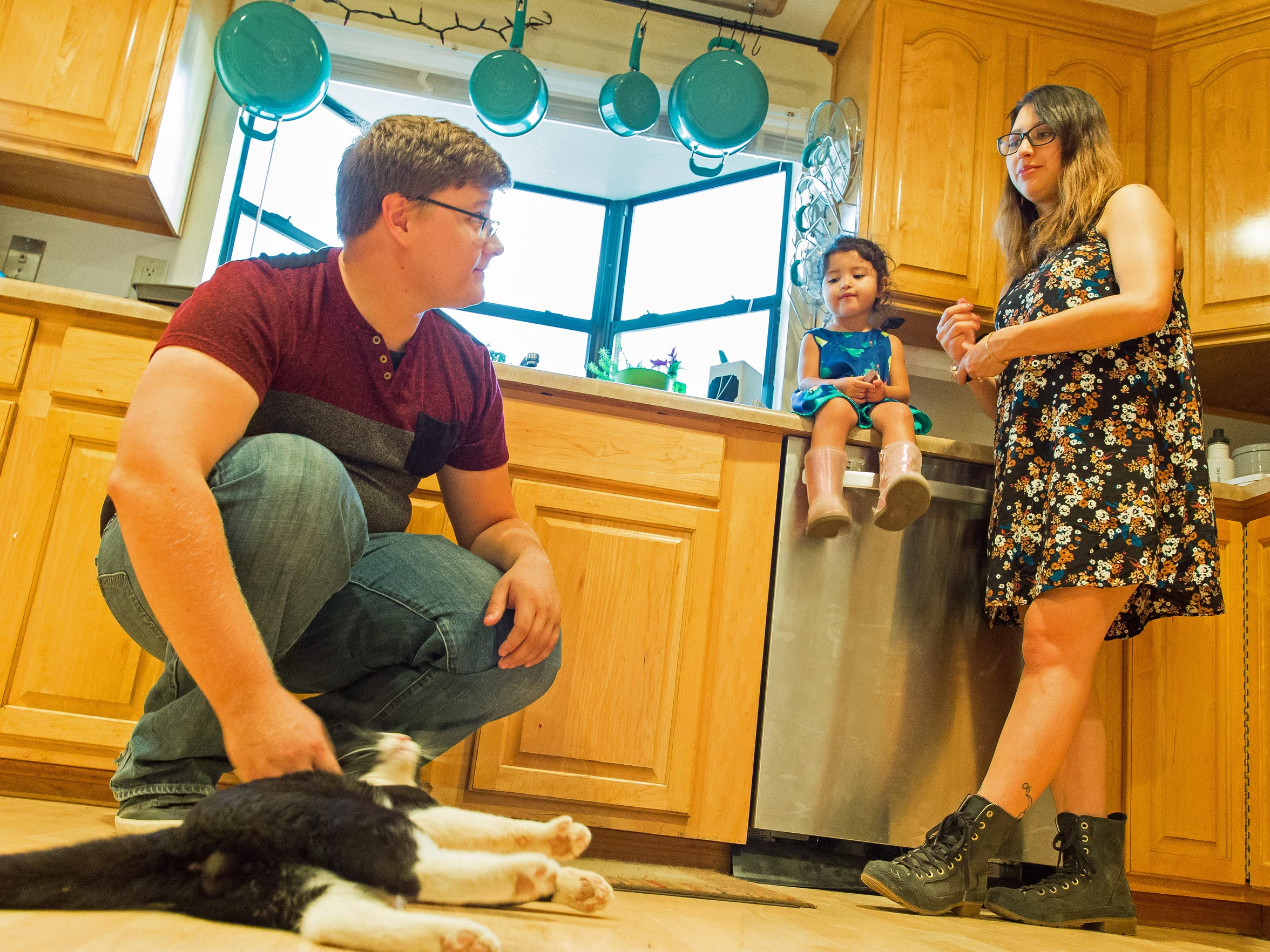 Zach Eason, 20, Luz Skywalker, 21, their daughter Luna, hang out with Charlie, the cat, in the kitchen of Zach's home on Tuesday.