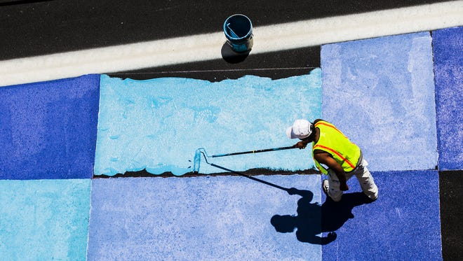 """June 20, 2017 - Artist Jonathan Golden paints a portion of Peabody Place, near S. Second St., as part of the Great Streets Pilot Project, a concept to """"create a safer and more attractive experience for pedestrians and cyclists in the heart of downtown,"""" according to the City of Memphis. The artistic approach for the project was envisioned by Memphis painter Anthony Lee, who is being funded by the UrbanArt Commission. Lee's long scale geometric patterns will stretch through eight intersections and three major blocks, from Front St. and Peabody Place, to King St. and Peabody Place.  The Great Streets Pilot Project was unveiled last month by the City of Memphis and the UrbanArt Commission. On-street parking is being subtracted from the sidewalk and curb to allow space for a two-way bike lane and new pedestrian plazas.   """"As a pilot project, it will be on the ground for one year. Over the course of that one year, we have performance metrics we'll be using to tell us to quantify how well it's performing,"""" said Nicholas Oyler, Bikeway and Pedestrian Program Manager, City of Memphis.  The three areas that will be examined from this study are safety, usage and economic development. """"So, we believe with the kinds of improvements that we're doing to the street, these interim improvements, we will make the street safer for everyone who uses it, rather they're on foot, on a bike, in a car."""" Oyler says the project will benefit businesses along the street with foot traffic for restaurants and bars and that more folks will walk or ride bikes downtown.  """"It's also creating a new seamless connection by bike from the Riverfront all the way into Midtown,"""" Oyler states. """"So, we're finally linking up a missing gap in our bicycle network.""""  For walkers, pedestrian plazas will be activated with outdoor and drinking areas.  A Volunteer Build Day is scheduled for Saturday, June 24, starting at 8 a.m., to assemble IKEA furniture on the corridor as well as landscaping and litter pick-up. A St"""